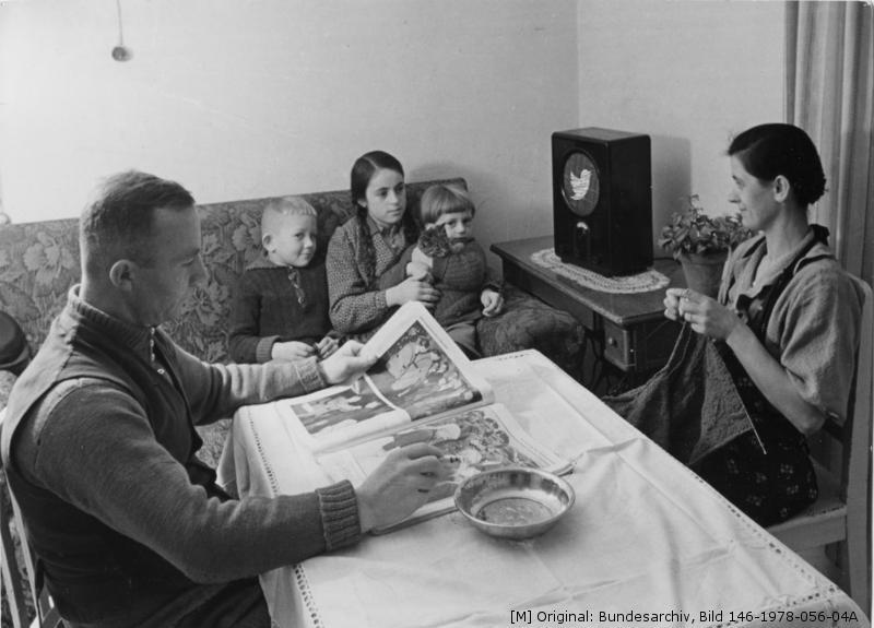 30er-Jahre-Familie sitzt um den Tisch und lauscht ihrem Volksempfänger, auf dem ein Twitterlogo prangt.